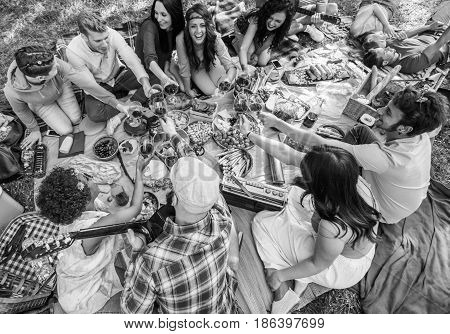 group of young  friends in picnic enjoy drinking wine eating and relaxing in a park sitting together. indie friends enjoy toasting wine, hippie style freedom and music. vintage  black and white image
