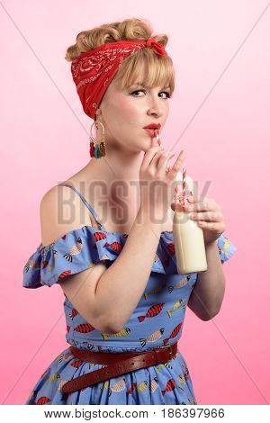 Cheeky pin up style shot of woman drinking milk
