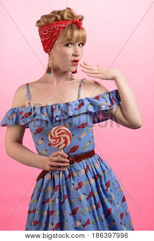 Cheeky pin up pose of woman with lollipop