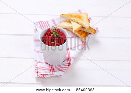 cup of fresh beetroot puree with toasts on checkered dishtowel