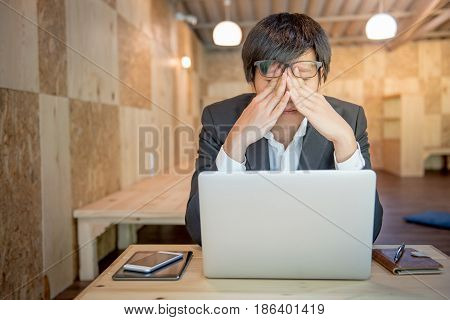 Portrait of young frustrated stressed business man with modern laptop computer and leather notebook on wooden office desk in workplace overworked and depression concepts Feeling sick and tired