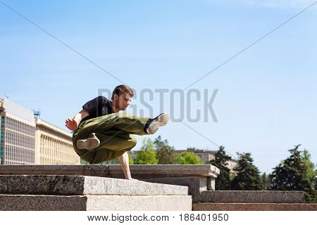 Young man jumping over the wall. Parkour in the urban space. Sports in the city. Sport activity.