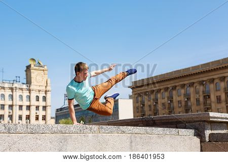 Young man jumps over the wall. Parkour in the urban space. Sport in the city. Sport activity.