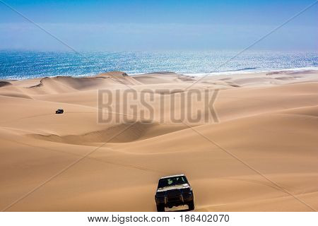 Fantastic jeep - safari through the huge sand dunes on the ocean shore. Atlantic coast of Namibia, south of Africa. The concept of exotic and extreme travel