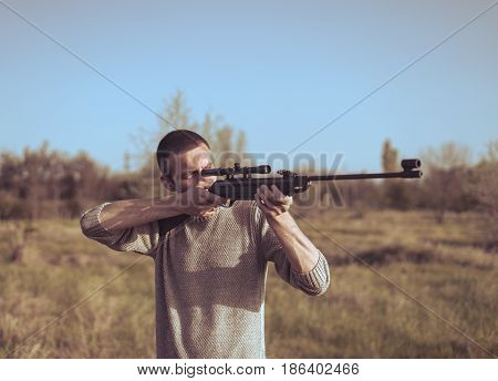 The man takes aim at the target with a sniper strikeball rifle. Retro toning colors. Selective Focus