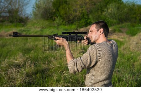The man takes aim at the target with a sniper strikeball rifle. Selective Focus. Side view