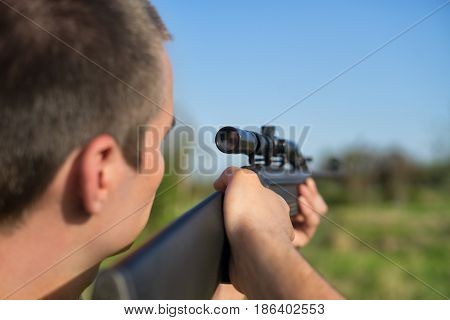 The man takes aim at the target with a retro sniper rifle. Selective Focus. Warm summer day