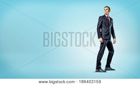 A businessman standing on blue background in half turn and looking over his shoulder. Way back and forward. Looking back in time. Business analytics.