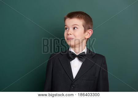 surpised school boy portrait near green blank chalkboard background, dressed in classic black suit, one pupil, education concept