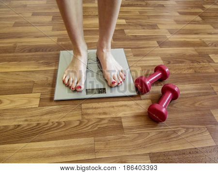 Two slender female legs stand on electronic scales. And two red dumbbells on the floor near the scales hint that the girl needs to watch the weight
