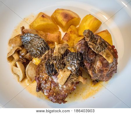 Roasted Pork With Mushrooms And Potatoes On White Plate
