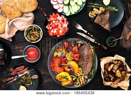 Different foods cooked on the grill on the wooden table grilled steak and grilled vegetables. Top view. Grill table concept