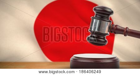 Hammer and gavel against 3d digitally generated japanese national flag