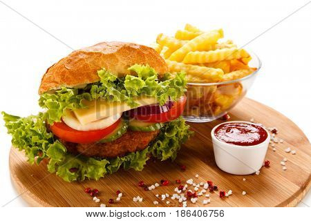 Big hamburger with french fries on white background