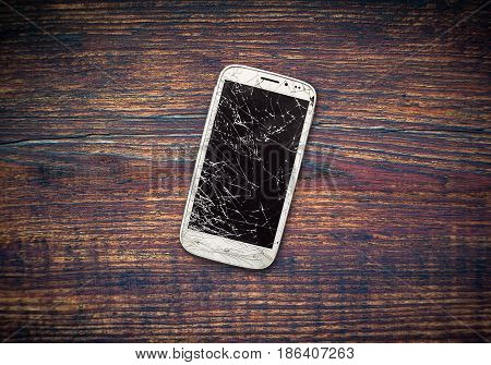 Phone with a broken display on a wooden table. Broken smartphone.