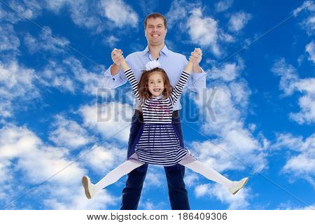 Happy young dad raise his beloved daughter's hands.