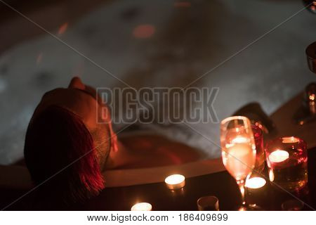 young handsome man enjoys relaxing in the jacuzzi with candles and champagne at luxury resort spa