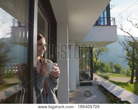 portrait of a young beautiful successful woman drinking coffee in the doorway of her luxury home villa