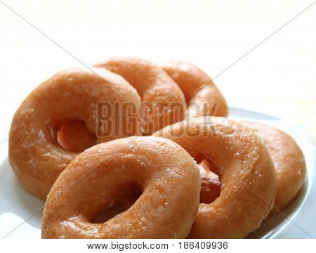 Closed up heap of sugar-glazed doughnuts served on white plate, isolated on white background