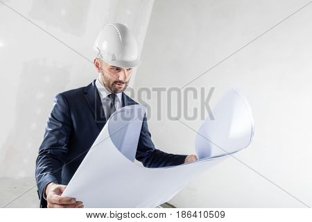 Business investor reading documents at the construction site. Wearing white helmet. Housing development and building industry.