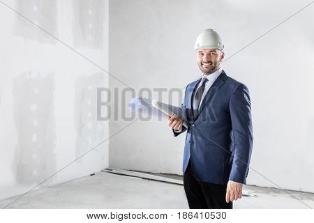 Business investor holding folded documents at the construction site. Housing development and building industry.