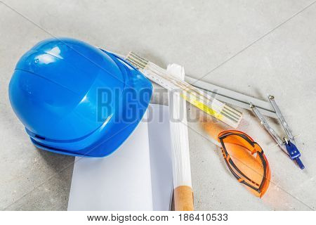 Hard hat, safety glasses and blueprints at the construction site. Building and engineereing tools close up.