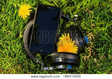 wireless travel headphones and smartphone on lawn with dandelions