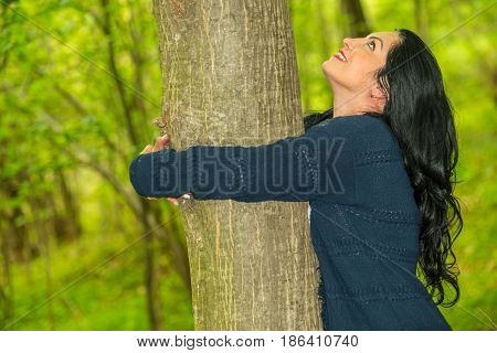 Happy woman embracing a tree and looking up