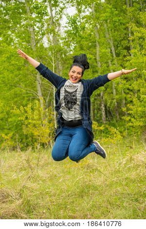 Laughing jumping woman in nature with forest in background