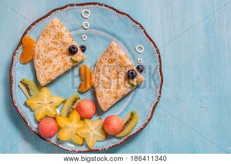 Funny crepes pancakes looks like a fish with fruits for kids breakfast