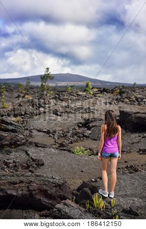 Woman hiking in volcanic rocks on volcano of Big island of Hawaii, USA. Tourist hiker walking on volcanic black rocks during summer traveling holidays.