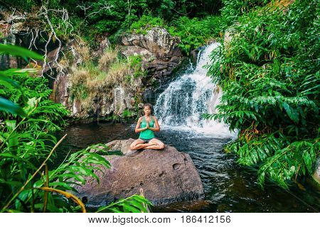 Yoga woman meditating at waterfall forest. Meditation in nature.Hawaii.