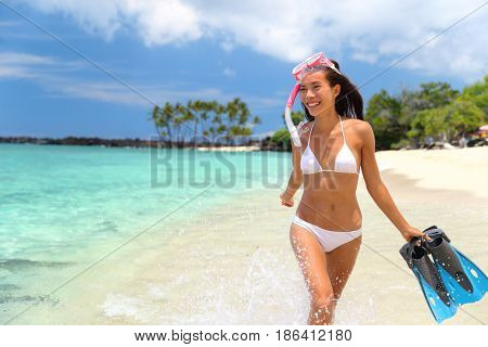 Happy beach vacation snorkeling girl having fun doing snorkel watersport activity on Hawaii beach. Asian woman enjoying swimming in tropical destination vacation travel on perfect beach.