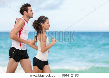Fitness interracial couple runners running on beach. Running couple jogging together outside on ocean background. Athletes training cardio outdoors working out.
