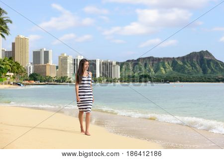 Waikiki beach Hawaii travel tourist woman relaxing walking on sand at sunset on famous beach stretch in Honolulu summer vacation destination in Oahu, Hawaii, USA.