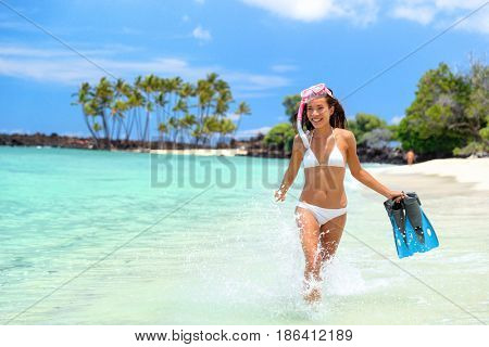 Summer beach vacation fun snorkel girl splashing water . Happy bikini woman relaxing in tropical ocean with fins and snorkeling gear. Exotic travel destination paradise in Big Island, Hawaii, USA.