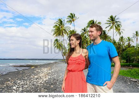 Hawaii couple enjoying beach holidays looking at view of ocean from black sand volcanic beach on Big Island of Hawaii, hawaiian travel vacation.