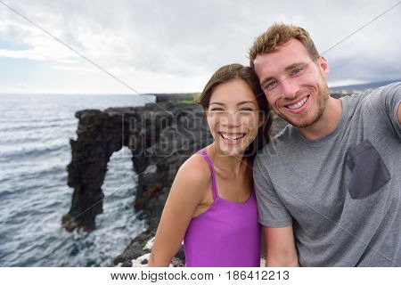 Selfie couple on nature travel Hawaii vacation. Young people taking phone picture at the Holei Sea Arch, tourist attraction on Big Island at the Volcanoes National park.