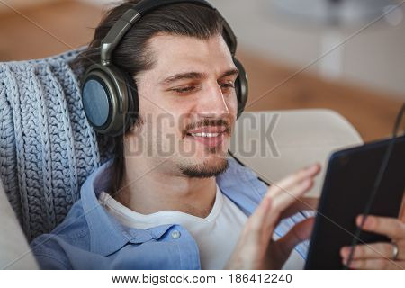 Handsome guy lying and listening to music on internet with dark blue tablet on sofa, closeup portrait