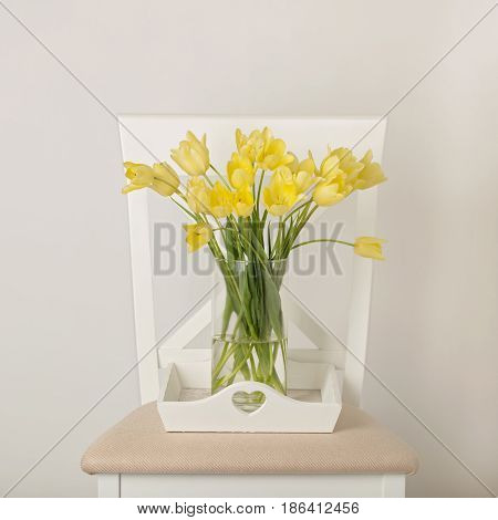 Yellow tulips in vase on white tray on the chair. Selective focus.