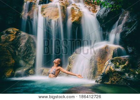 Wellness spa waterfall woman with open arms in freedom relaxing in nature waterfall. Relaxation in paradise tropical vacation. Hawaii holiday destination.