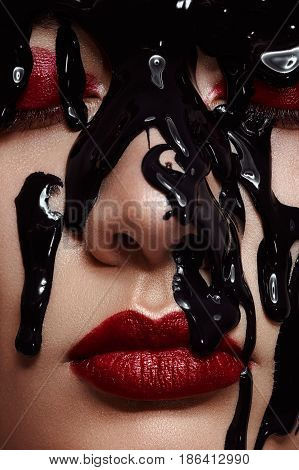 Close up Woman Face with dark red Lips and Black Paint