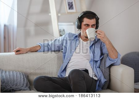 Handsome bearded guy sitting on sofa with headphones and drink tea from mug