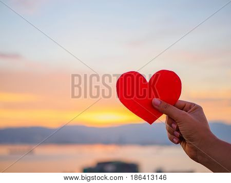 hand is raising the red paper heart with blur sunlight during sunset Valentines day