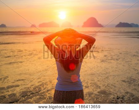 Woman wearing hat with open arms under the sunrise near the sea