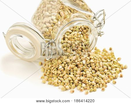 Raw green buckwheat in bank isolated on white background. Healthy food and diet concept