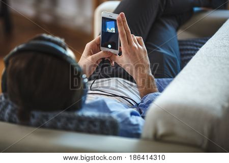 Handsome guy lying on sofa with smartphone, back view, focus on smartphone