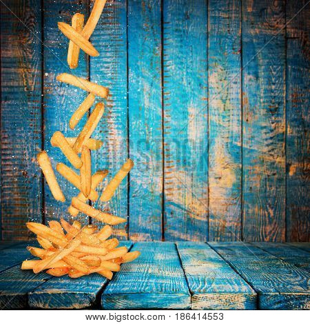 French fries in freeze motion. flying fried potatoes on old wooden background.