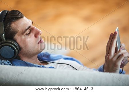 Handsome guy lying on sofa with smartphone, side view, copy space