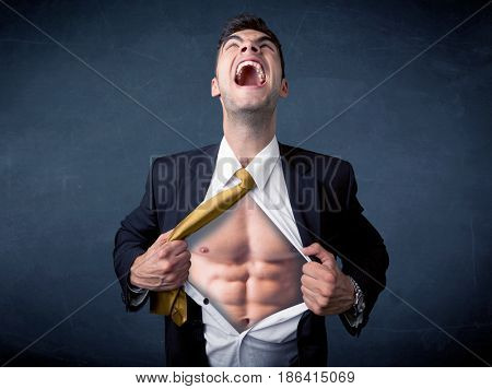 Businessman tearing off his shirt and showing mucular body concept on background